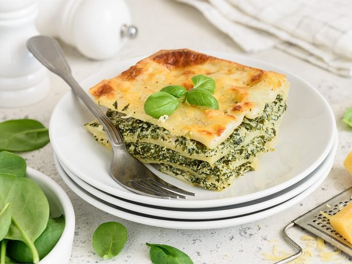 A piece of lasagna with spinach, ricotta and bechamel sauce on a white plate. Traditional italian dish. Selective focus.