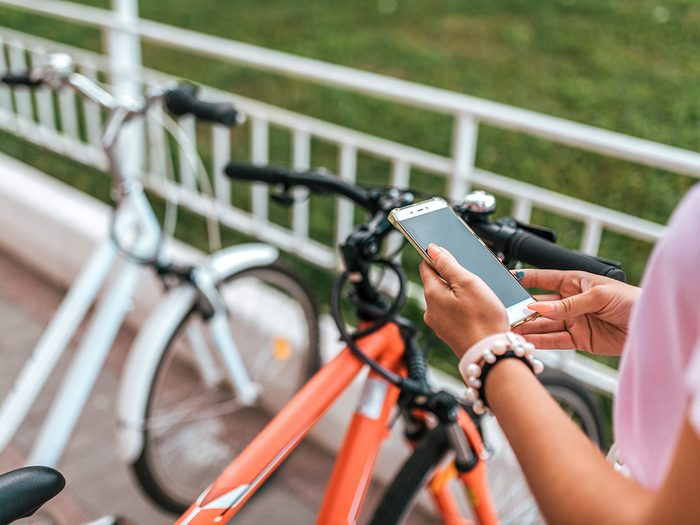 Bike theft prevention tips - In summer city background parking bicycles girl chooses route application, Internet online map phone. Route bike path. Bicycle parking city. Rental and blocking, protection application Internet.