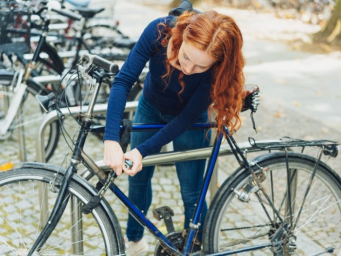 Trendy,young,redhead,woman,chaining,her,bicycle,to,a,metal