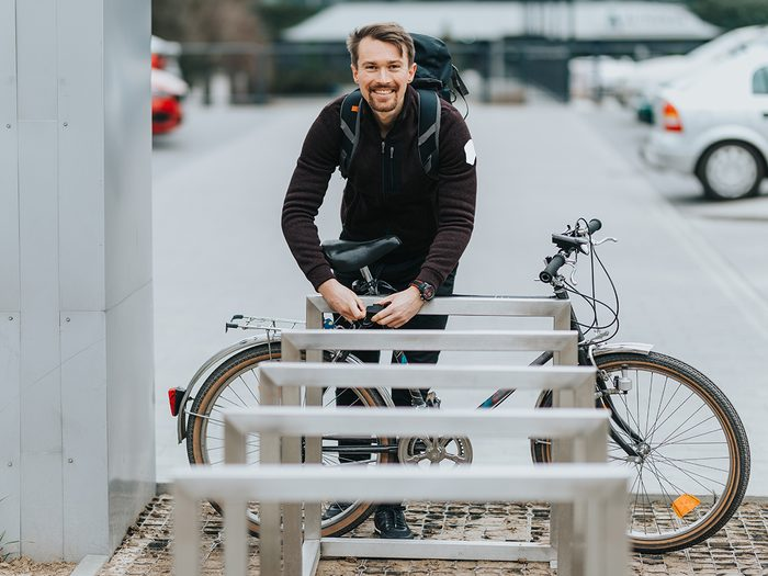 Bike theft prevention tips - man protects his bike from theft. He pins it with a lock to the steel railing