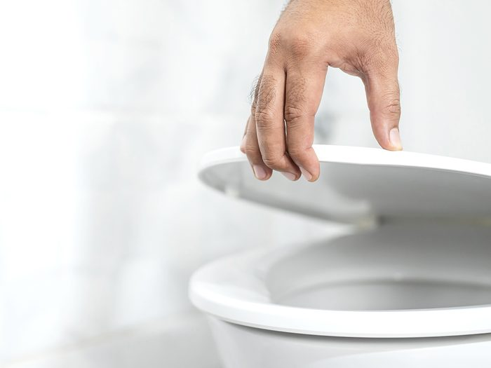 Cloudy urine - close up hand of a man closing the lid of a toilet seat. Hygiene and health care concept.