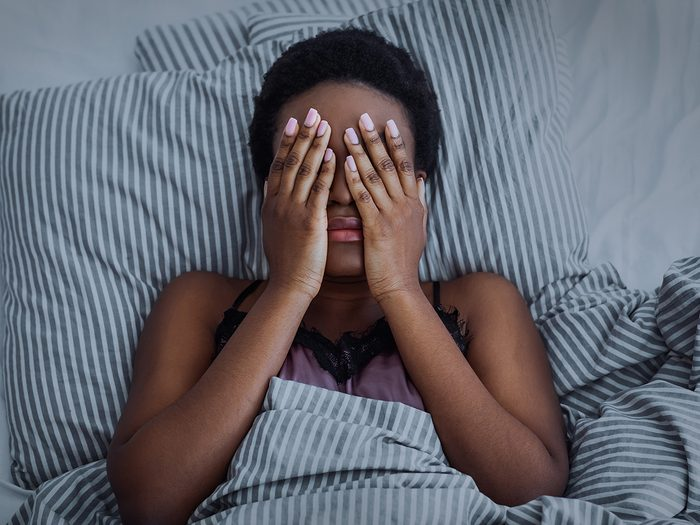 Common sleep problems - Woman with insomnia in bed
