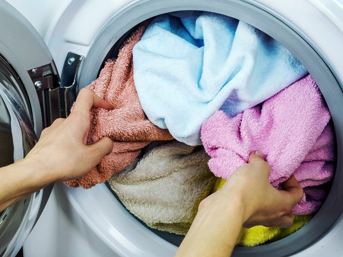 How to separate laundry - Woman gets clothes from the washing machine
