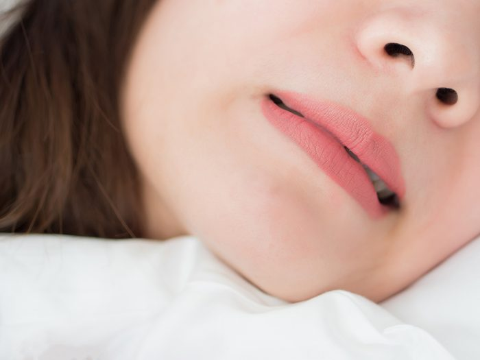 How to stop grinding your teeth - woman bruxing in sleep