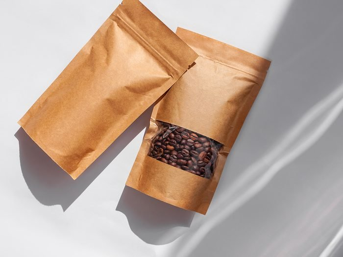 Brown kraft paper pouch bags with coffee beans top view with shadow isolated on white background. Packaging for foods and goods template mockup.Pack with clasp and window for tea leaves weight product