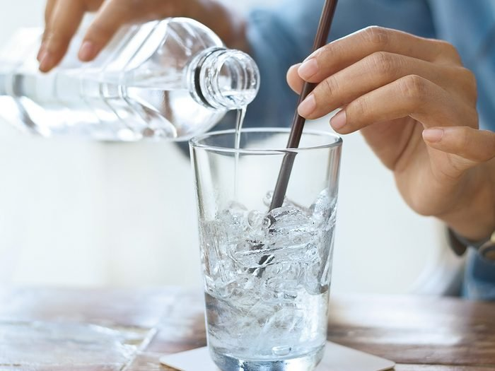 woman drink water with ice in glass on a table in restaurant background