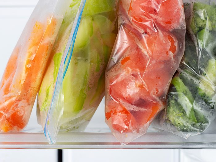 Things in your freezer you should toss - Frozen vegetables in plastic bags in the freezer close-up.