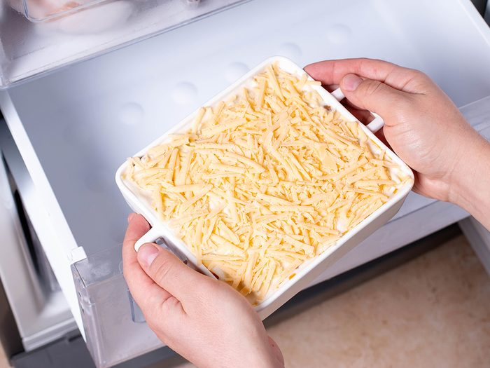 Frozen ready meals. Man's hands are taking frozen casserole from the freezer of the fridge. Concept of ready made frozen dishes and saving time on cooking food.