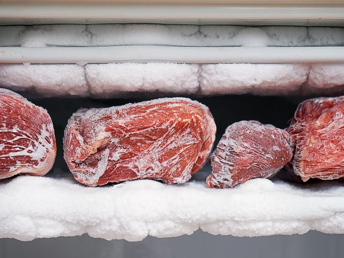 Things in your freezer you should toss - Big chunks of red beef lying on the freezer shelves with a big quantity of frozen ice and snow. This freezer hasn't been thawed in a long time.