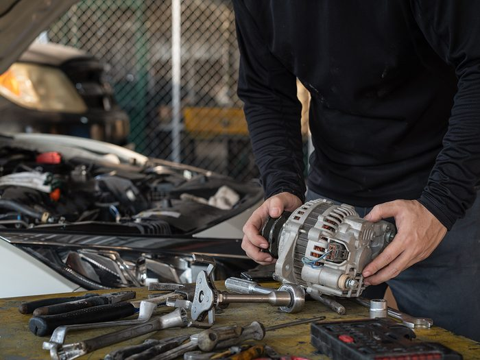 things you should never do to your car - Mechanic man holding alternator of the car on working table in repair and maintenance garage