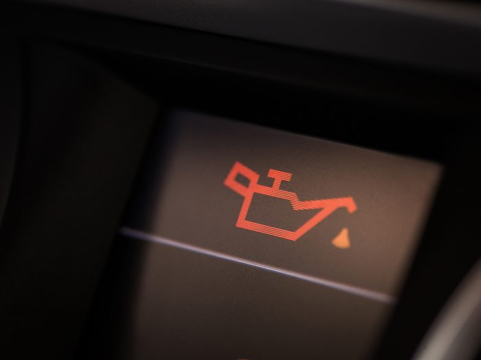 things you should never do to your car - Detail of the dashboard of a car, with the oil alert icon lit up