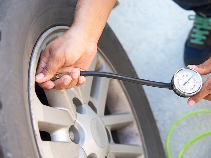 things you should never do to your car - man checking air pressure and filling air in the tires of his car