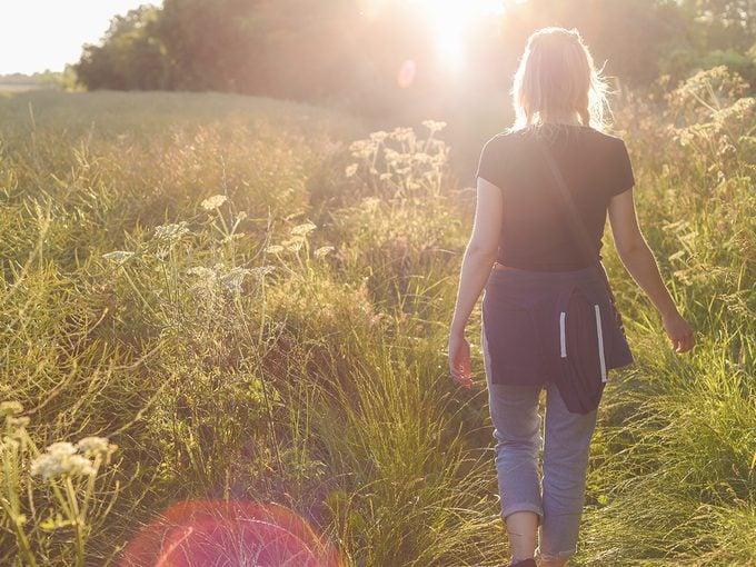 Walking meditation - woman walking through field