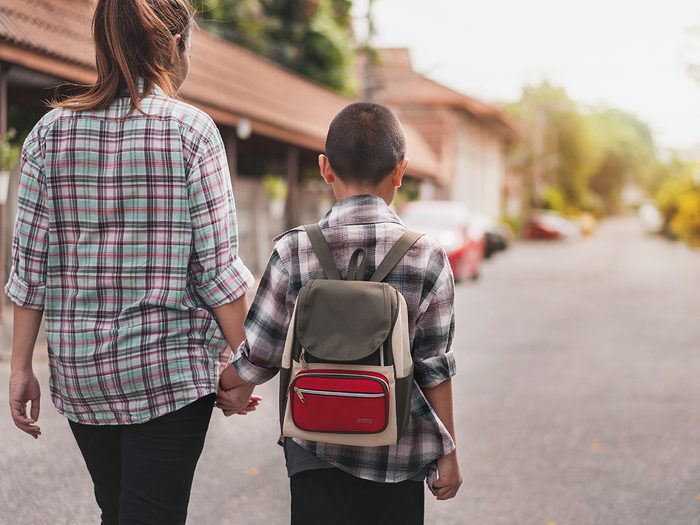 Rare genetic condition medical mystery - Mother or parent holding hand son or pupil with backpack go to school, Back to school concept, Selective focus.
