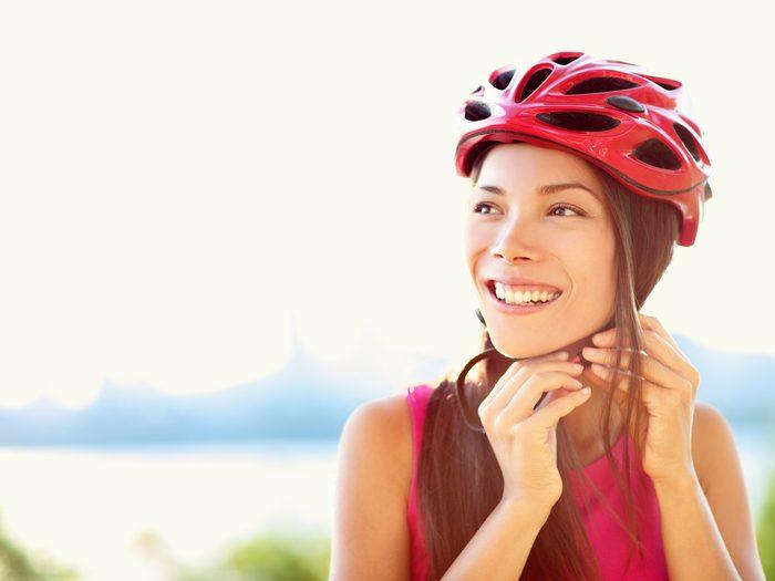 how to buy a bike - woman putting on bike helmet